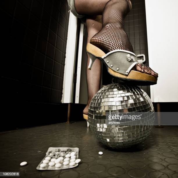 Woman's Leg Resting on Disco Ball in Bathroom Near Pills