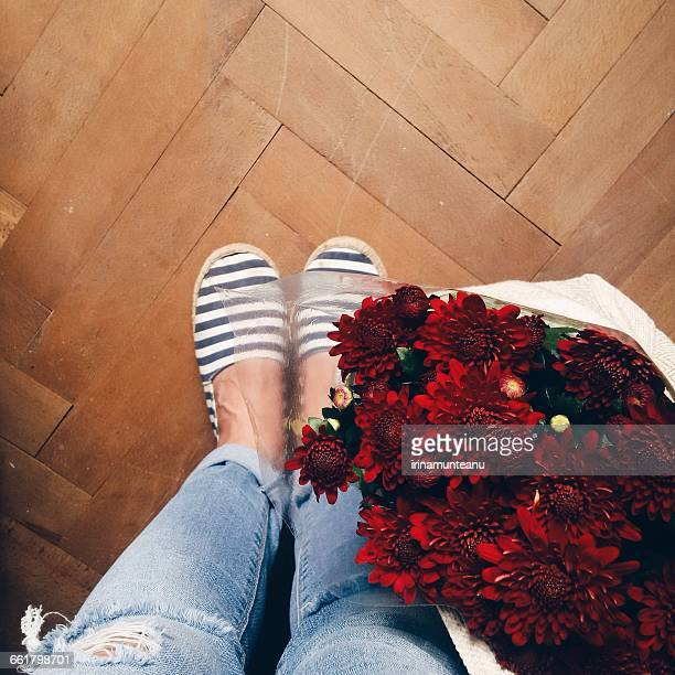 Woman's legs and flowers in  a bag