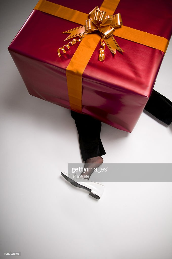Woman's Legs Crushed Underneath Huge Present : Stock Photo