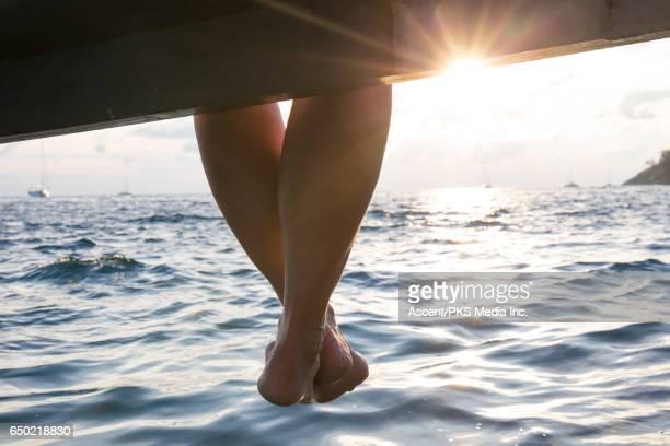 Woman's legs dangle from pier, sun rises over sea