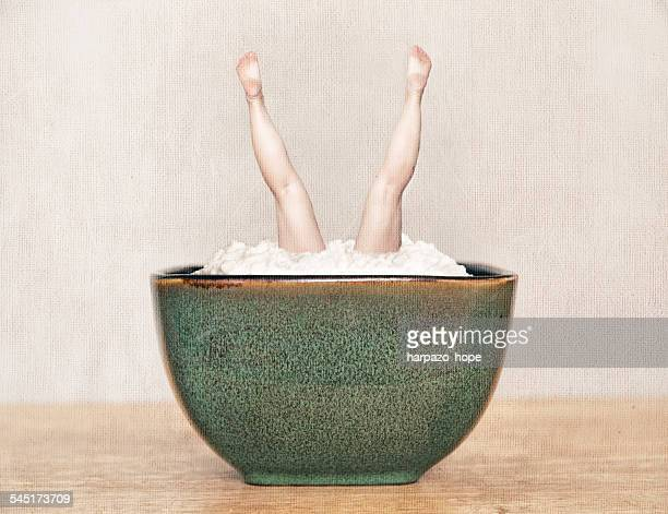 Woman's legs in a bowl of cottage cheese