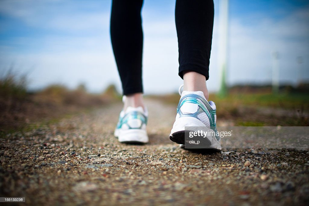 Woman's legs in black tights and white running shoes on dirt : Stock Photo