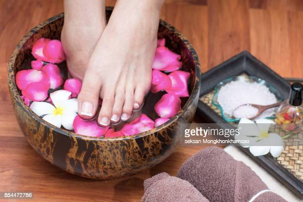 Woman's legs in blue water on spa treatment surrounded by towels and candles.
