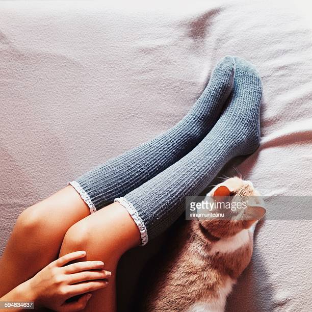 Woman's legs in long socks and cat lying on a bed