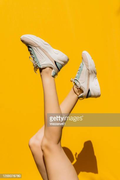 woman's legs in sports shoes over yellow wall during sunny day - schuhwerk stock-fotos und bilder