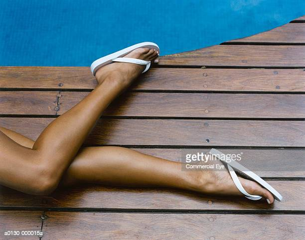 woman's legs on pool deck - sandal stock pictures, royalty-free photos & images