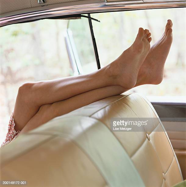 Woman's legs over car seat, low section