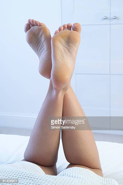 womans legs raised, in bedroom, ankles crossed - woman lying on stomach with feet up stock photos and pictures
