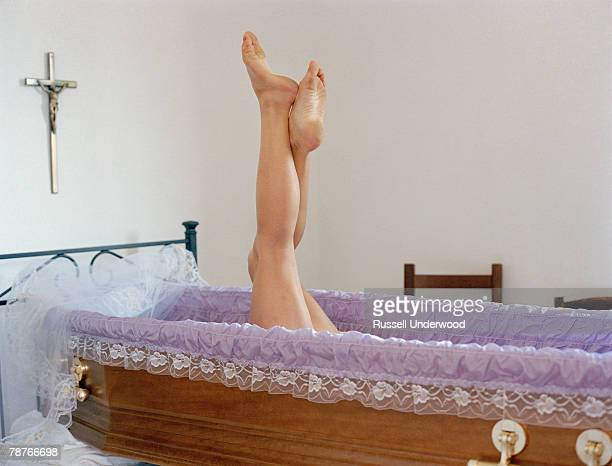 a woman's legs raising out of an open coffin - begräbnis stock-fotos und bilder