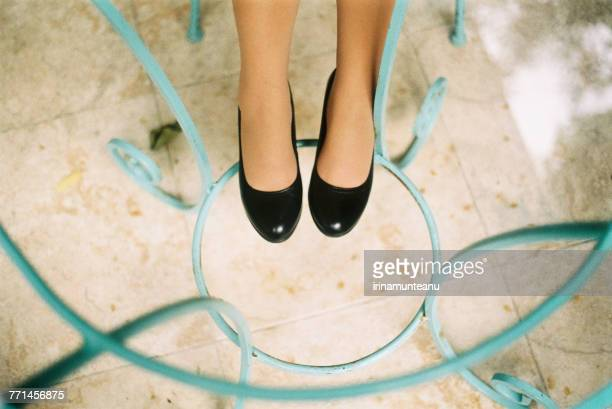 womans legs resting on a metal table frame - pump schoen stockfoto's en -beelden