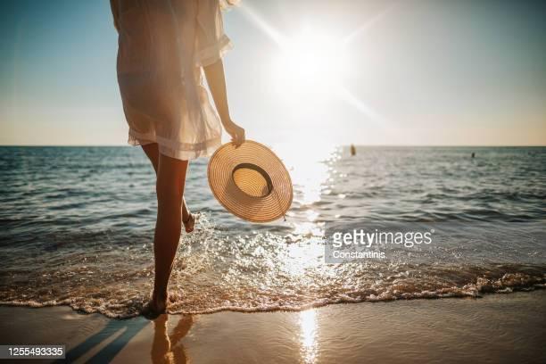 gambe da donna che spruzzano acqua sulla spiaggia - spiaggia foto e immagini stock
