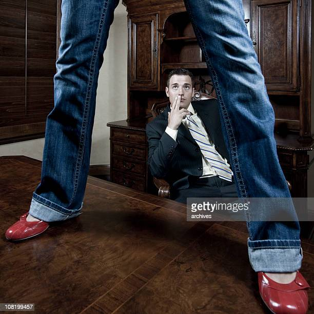 woman's legs standing on businessman's desk while he watches - women spreading their legs stock photos and pictures