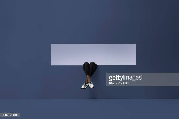 womans legs sticking out of rectangular opening in coloured wall and looking up - blue shoe stock pictures, royalty-free photos & images