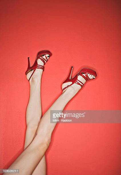 woman's legs up in air wearing red high heels - hoge hakken stockfoto's en -beelden