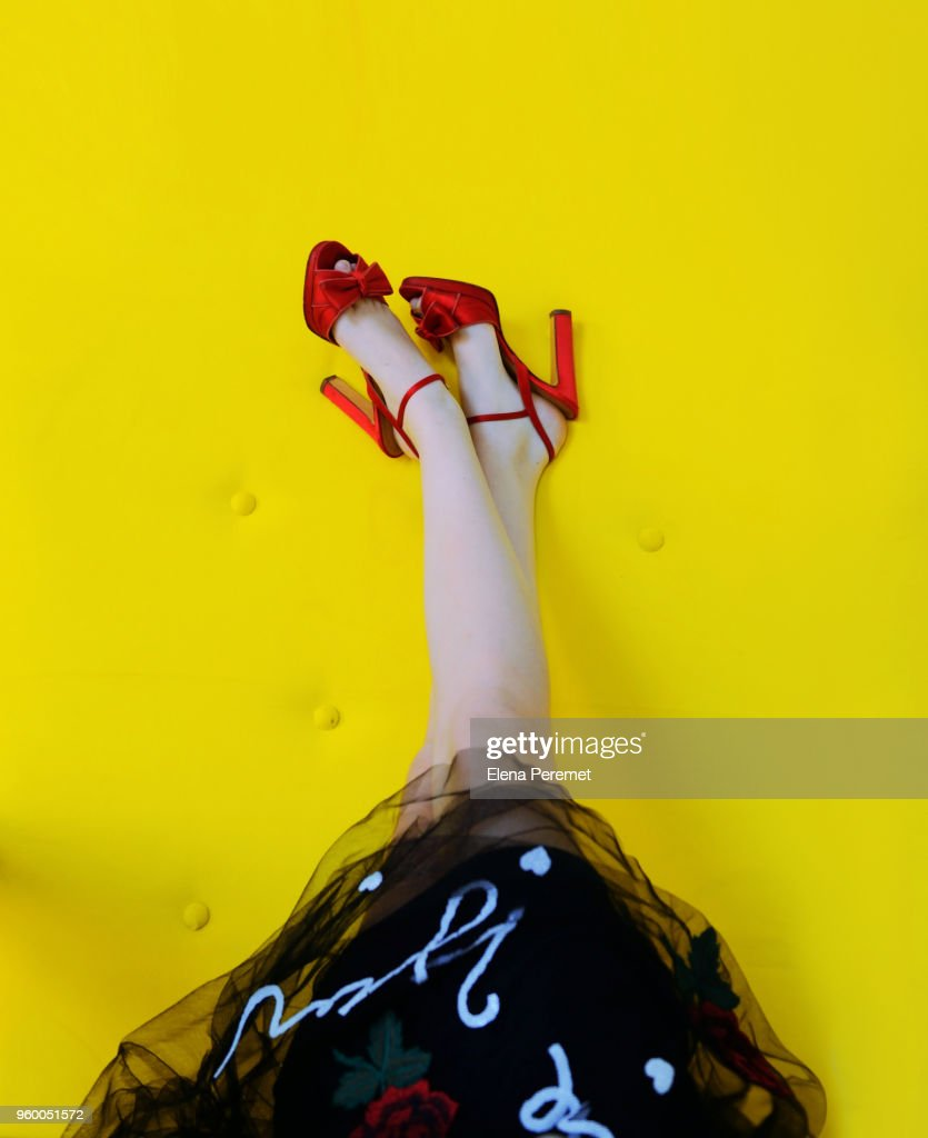 Woman's Legs Up  wearing Red High Heels on yellow background : Stock Photo