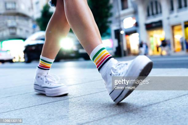 woman's legs walking down the street with a car in the background - 人の足 ストックフォトと画像