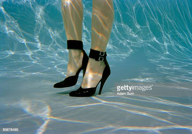 a woman's legs wearing high heels underwater - palm springs stock-fotos und bilder