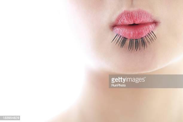 woman's lip with false eyelashes