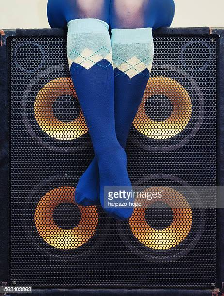 Woman's lower body sitting on a bass cabinet.
