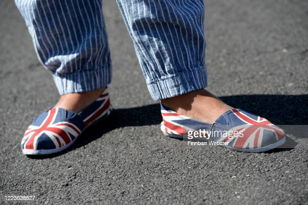 Woman's patriotic Union Jack shoes are on show during a street party on May 08, 2020 in Dorchester, United Kingdom. The UK commemorates the 75th...