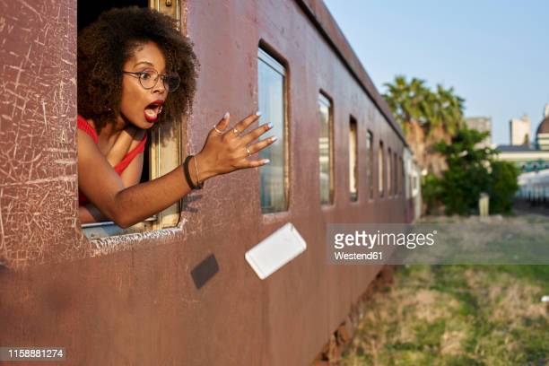 woman's phone falling out of train window - caer fotografías e imágenes de stock