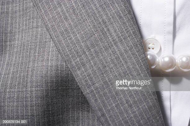 Woman's pinstripe suit jacket, button down shirt and pearl necklace