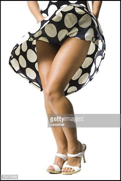 woman's polka dot dress blowing in breeze - skirt blowing stock photos and pictures