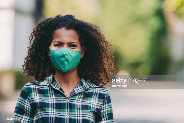 woman's portrait with protective face mask covid-19 - greenpeace stock pictures, royalty-free photos & images