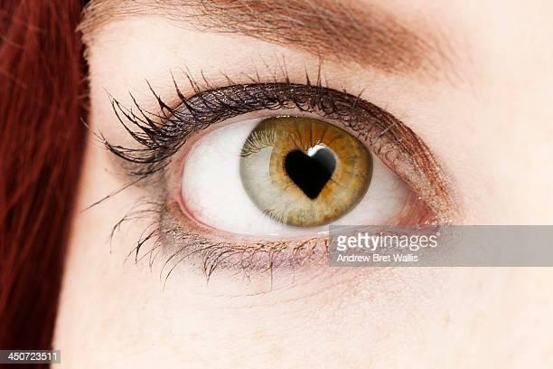 woman's pupil forms the shape of a love heart - occhi nocciola foto e immagini stock