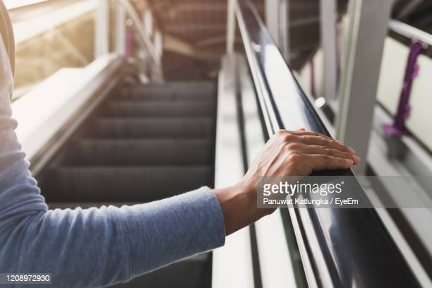 woman's right hand on the escalator handrail on the train station - railing stock pictures, royalty-free photos & images