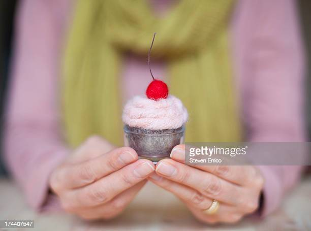 Woman's showing her completed cupcake craft