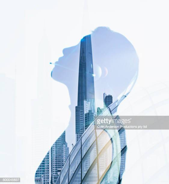 Woman's silhouette in reflection of city skyscrapers