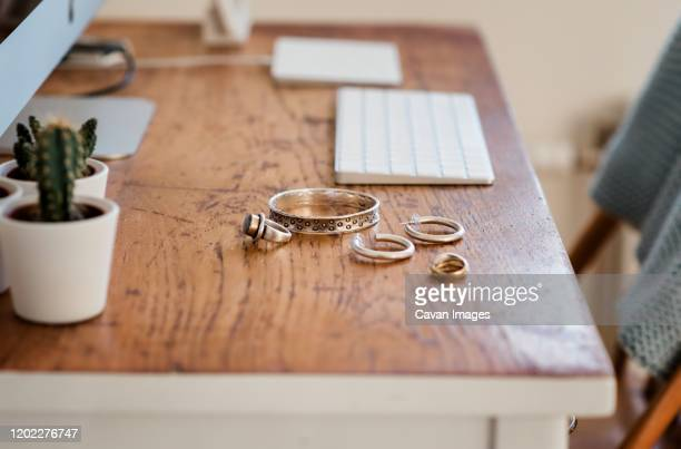 woman's silver jewellery on a desk next to a computer - jewellery stock pictures, royalty-free photos & images