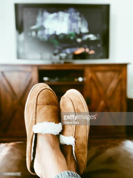 woman's slippered feet on ottoman in front of tv - comfortable stock pictures, royalty-free photos & images