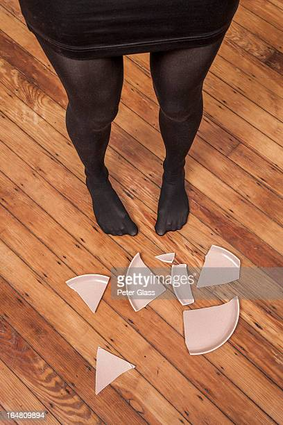 Woman's stocking feet next to a broken plate