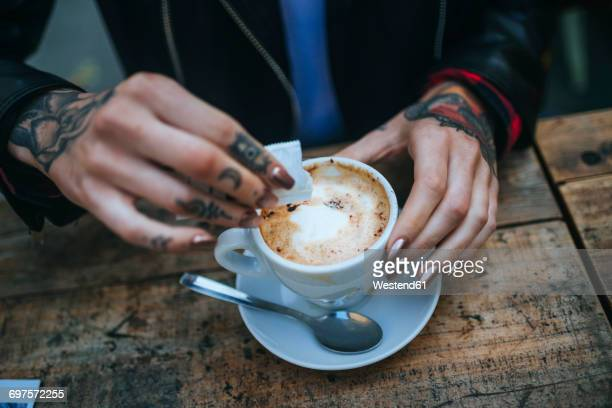 woman's tattooed hands pouring sugar into cup of coffee, close-up - sugar coffee stock photos and pictures