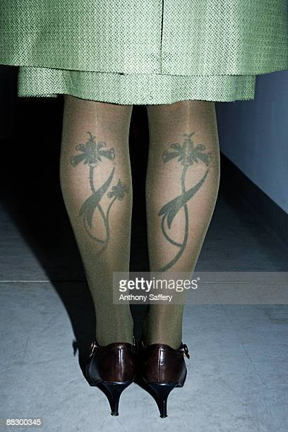Womans tattooed legs under nylons