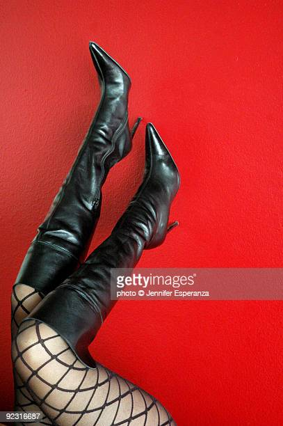 Woman's thighs in fishnet stockings with boots