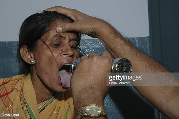 Woman's tongue is examined by Doctor Bhagwat, on staff with the Assembly of God Hospital in Kolkata, India. The church provides several free rural...