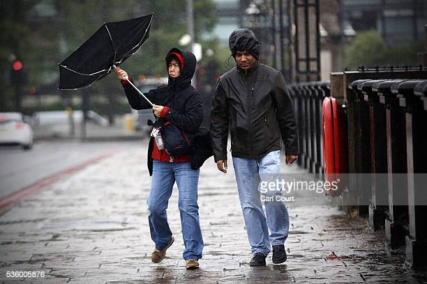 A woman's umbrella is blown inside out as she crosses a bridge in rain and wind on May 31 2016 in London England Heavy rain hit parts of England...