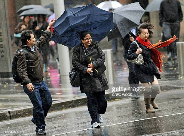A woman's umbrella turns inside out as she struggles to walk into the wind at Circular Quay in Sydney on June 15 2011 Damaging winds and heavy rain...