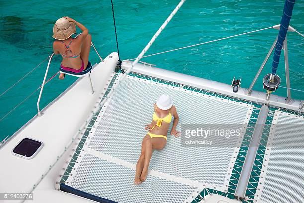 womem relaxing on catamaran in the caribbean - catamaran stock photos and pictures