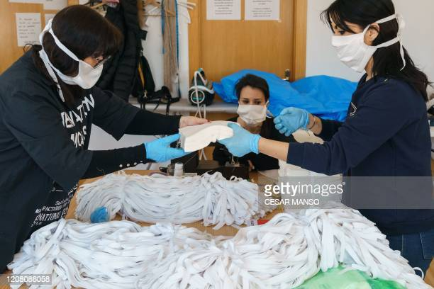 Womem sew handmade face masks at a workshop in Burgos northen Spain on March 24 amid concerns of the COVID19 coronavirus outbreak Another 514 people...