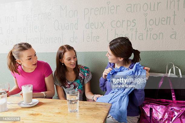 women admiring clothes in cafe - stefanie grewel stock-fotos und bilder