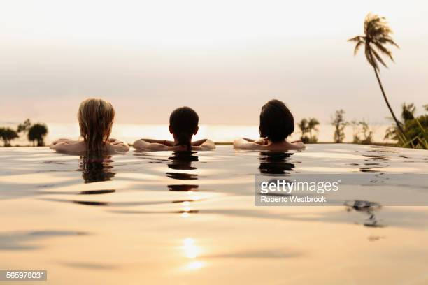 Women admiring scenic view in infinity pool