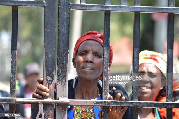 Women affected by the post poll violence look on through an iron gate after hearing of the main case to seek compensation was suspended pending...