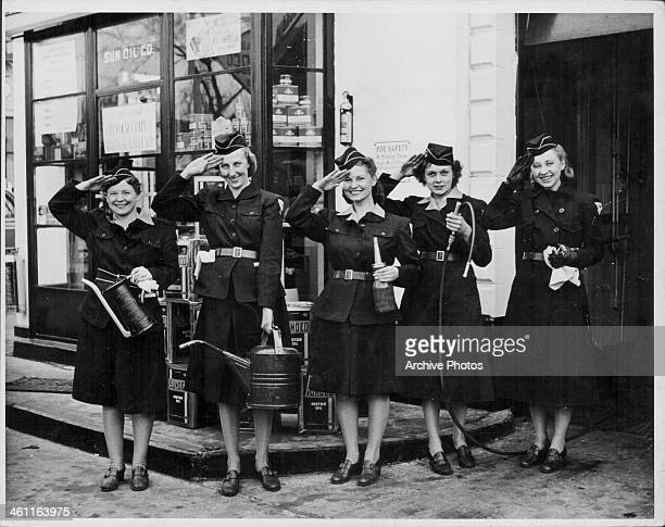 US women aiding the war effort during World War Two Civil Defense volunteers saluting outside a gas station circa 1944