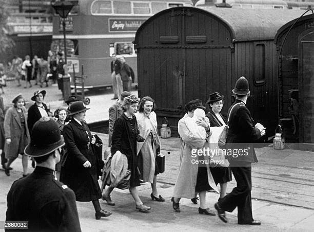 Women aliens leave for the Isle of Man escorted to trains by police and officials at a London station