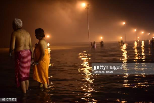 a women along with husband taking a holi dip  during ganga sagar fair - ganga sagar stock photos and pictures