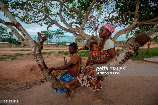 Women and a child rest in a tree in the community of Ntocota, Metuge District in Pemba, Cabo Delgado Province on February 22 where thousands of...